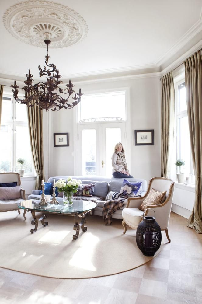 Organiske former. Den buede Howard-sofaen kler rommets buede form. Putene i den er fra Riis interiør og Country Chic. Paljettpute fra Milla Boutique. Lykten er fra Villa Collection. Gardinene i olivenfarget silke er tilpasset av gardinekspert Sara Dahl, som har sydd alle gardinene i leiligheten.