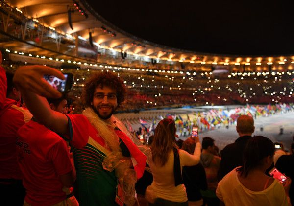 """A spectator takes a """"selfie"""" picture during the closing ceremony of the Rio 2016 Olympic Games at the Maracana stadium in Rio de Janeiro on August 21, 2016. / AFP / Ed JONES"""