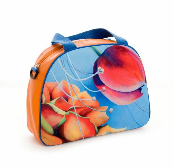"""Artbag """"Orange"""" displays Dutch floral art on outdoor textile on one side of the bag. Shoulder bag with detachable handles, zipper inside. Four studs on the bottom of the bag help it stand upright. Orange-coloured artificial leather, with blue hand- and shoulder straps. Price: 60 euro excl transport costs. Order via info@florifique.com."""