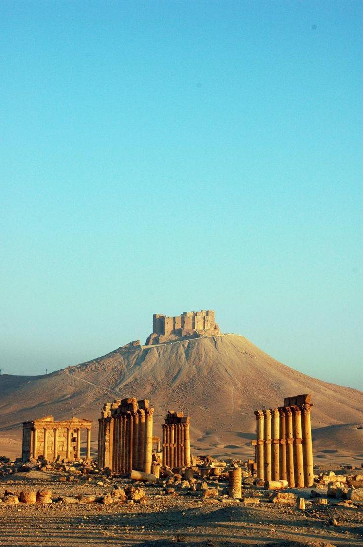 """Pelo Mundo...  Palmira, hoje Tadmor, era uma antiga cidade na Síria central, localizada num oásis a cerca de 210 km a nordeste de Damasco. A localização estratégica da cidade, aproximadamente a meio da distância que vai do mar Mediterrâneo até ao rio Eufrates, tornou-a num ponto de paragem obrigatório para muitas das caravanas que seguiam aí a sua rota comercial. O nome """"Palmira"""" refere-se, tal como o prenome feminino, às palmeiras — árvore que supostamente existiria aí em grande quantidade."""