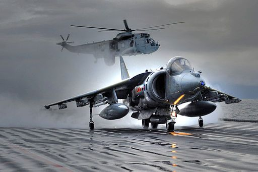A Harrier GR9 takes off from HMS Ark Royal for the very last time, whilst a Seaking helicopter hovers in the background. (This image has been digitally manipulated for artistic effect.)