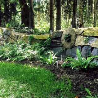 Fertig bepflanzte Natursteinmauer : Garten im Landhausstil von Staudengärtnerei Gaissmayer