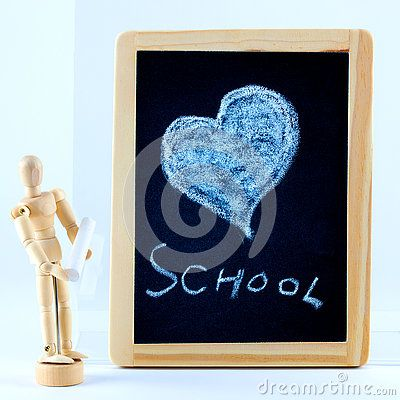 A blackboard with a chalk drawing of a heart and the word school and a little…