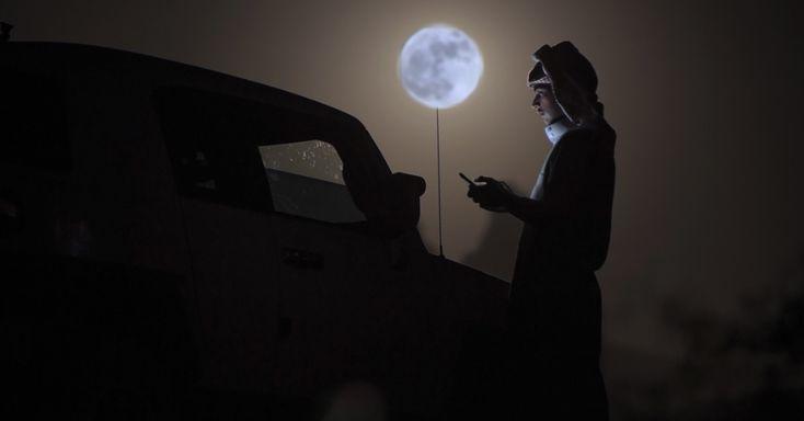 Homem verifica o celular sob a luz da superlua em deserto perto de Tabuk, na Arábia Saudita