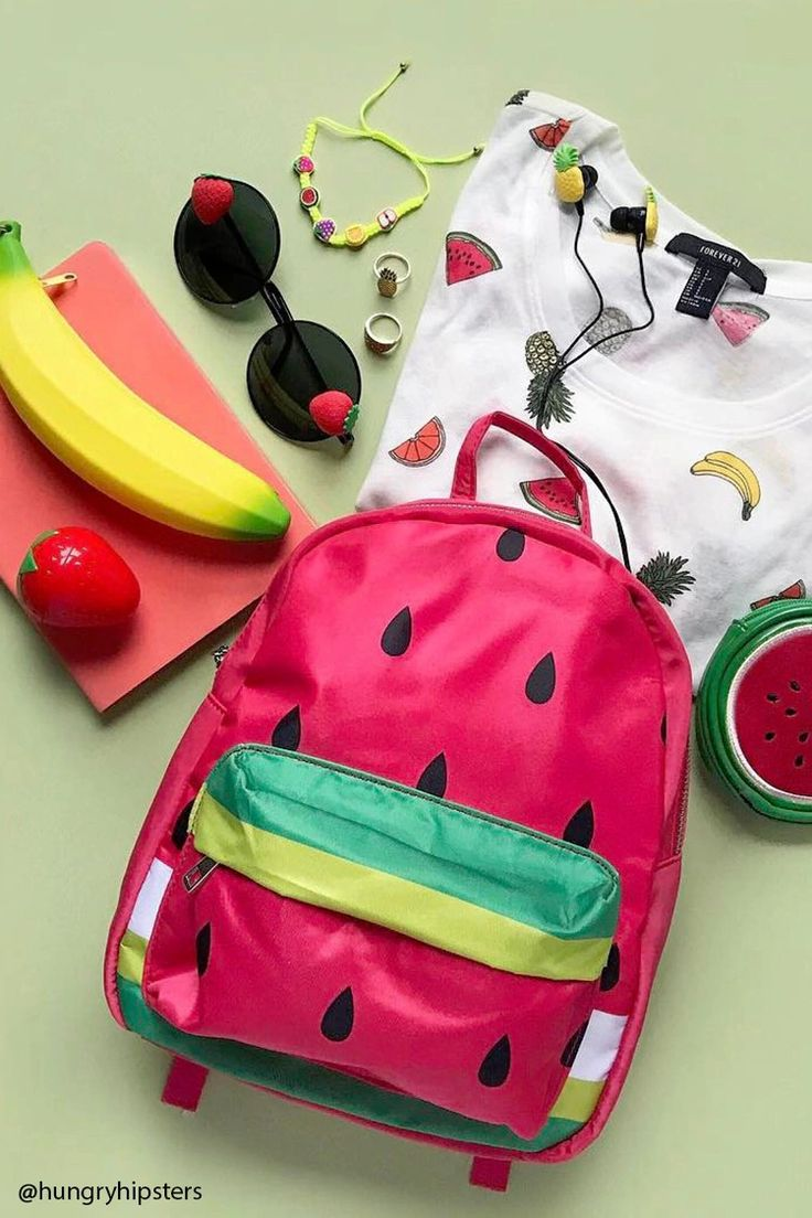 A structured mini backpack featuring an adorable watermelon design, a top handle, a zippered top closure, adjustable shoulder straps, an exterior zippered pocket, and an interior slip pocket.