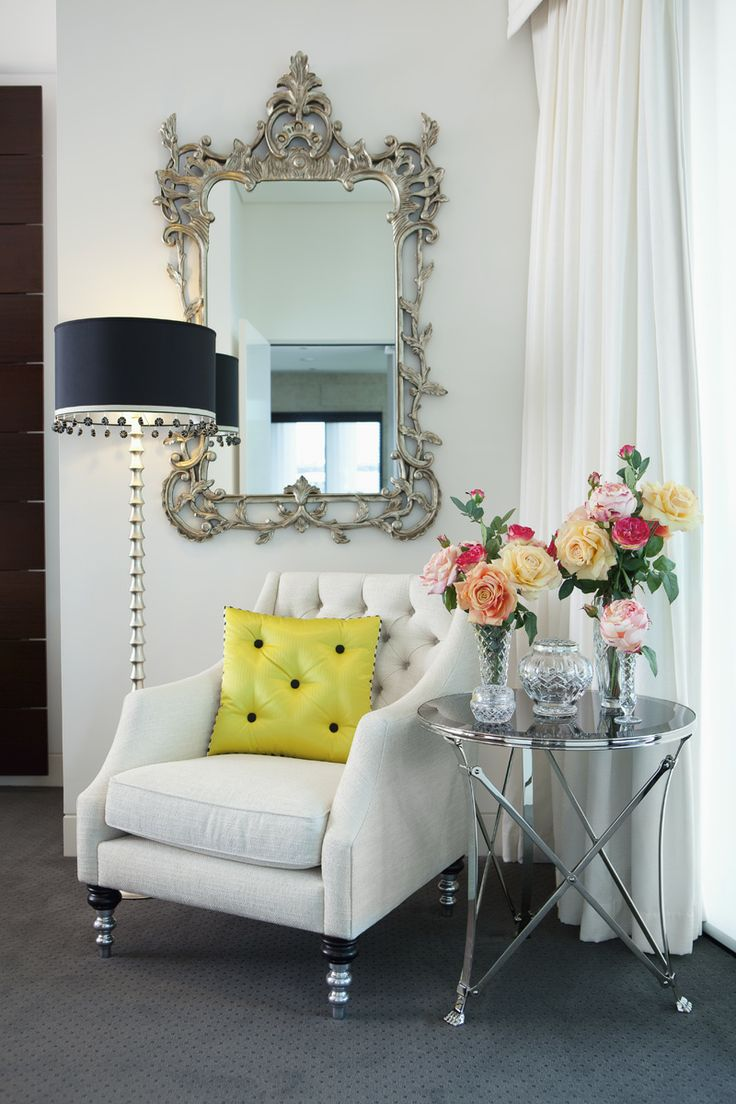 A small nook in a Master Bedroom featuring an upholstered armchair with chrome legs, decorative silver leaf mirror, floor lamp and chrome side table with a black glass top.