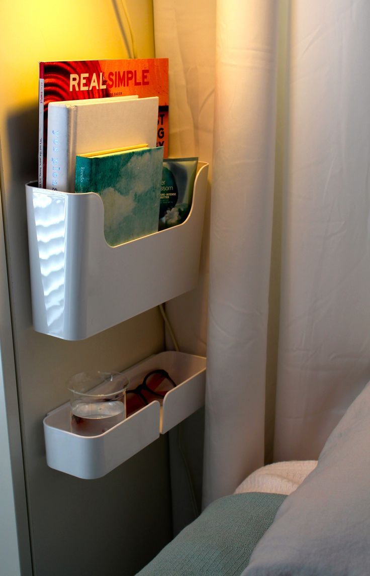 No room for a night stand? We hung these IKEA Pluggis containers on a bedside armoire.