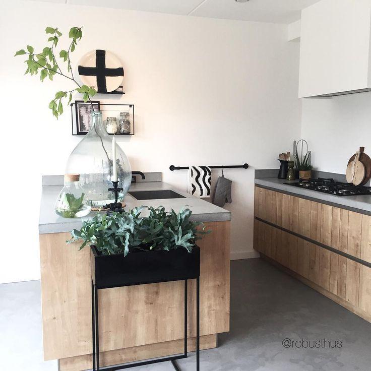 Betonlook vloer, houten keuken, betonlook aanrechtblad, rail met s-haakjes voor theedoeken e.d., afzuigkap in schouw weggewerkt, grote flesvaas met tak (@robusthus)