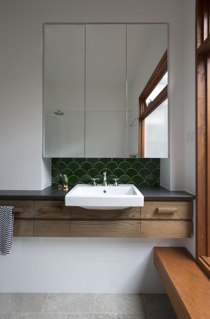 Beautiful deep green fishscale tiles are set against solid timber in the bathroom. Brooke Aitken Design