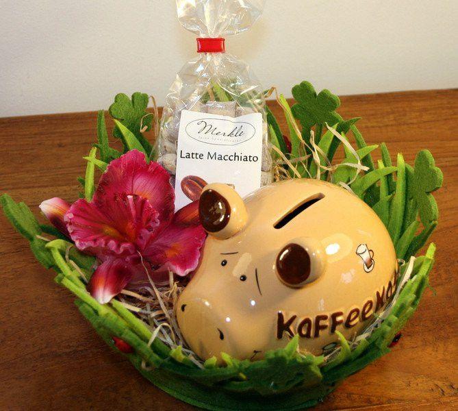 """Kaffeetrinker Geschenk - Kaffeekasse <p>Zum Kaffee eingeladen und auf der Suche nach einem passenden Mitbringsel?<br>  <br>  Mal etwas anderes als Blumen """"Geschenkkorb für Kaffeetrinker"""" gefüllt mit den folgenden Geschenken:<br>  - Sparschwein """"Kaffeekasse""""<br>  - Große Kerze in Form einer Orchidee<br>  - Latte Macchiato Bonbons<br>  <br>  Ein lustiges und zugleich gut brauchbares Geschenk!</p>"""