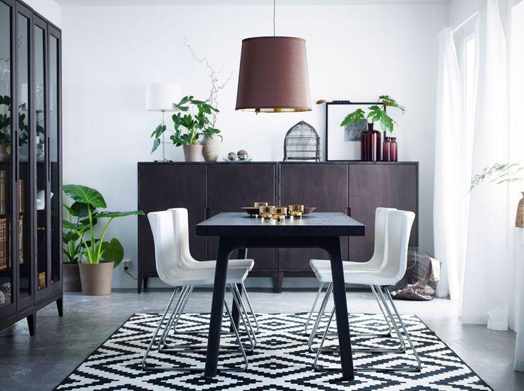 Salle à manger lumineuse avec une table noire et des chaises en cuir blanc à pieds chromés,  combinées à des armoires et des vitrines en brun.