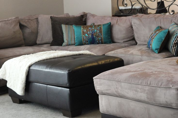 Microfiber tan sectional living room with brown leather ottoman and blue and brown accent ...
