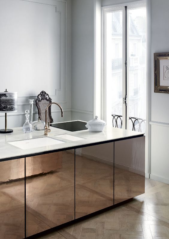 Bronze mirrored finish at kitchen island face. Calacatta marble at countertops.