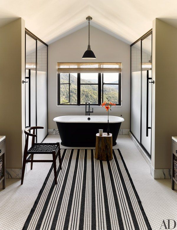 A Waterworks tub and a West Elm chair in a guest bath | archdigest.com
