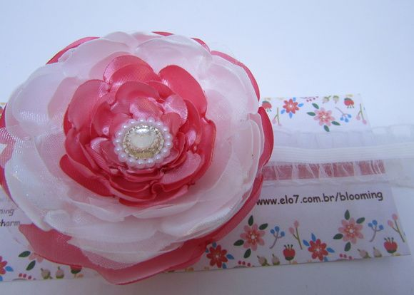 Faixa infantil de elástico de renda fininho com uma flor de cetim em rosa e branca.