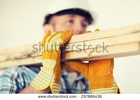 repair, building and home concept - close up of male in gloves and helmet carrying wooden boards on shoulder - stock photo