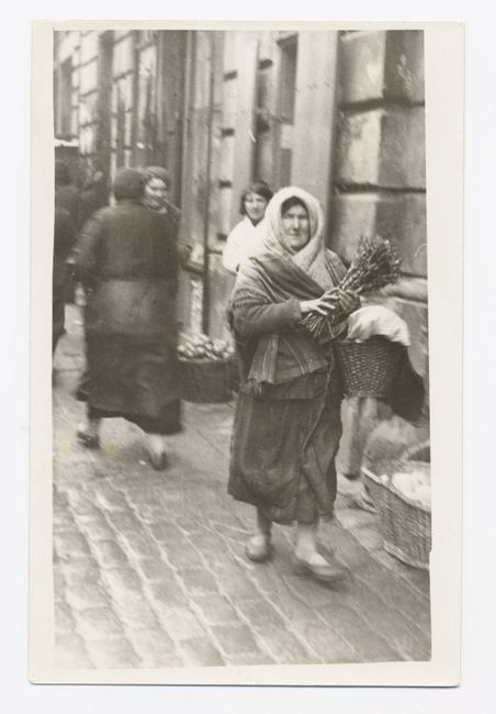 Warszawa, 1930s. On the eve of Sukkot, a women carries a bundle of hosha'anot and a covered basket, along a commercial street.