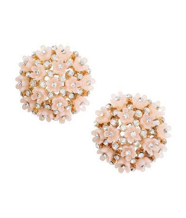 Ljusrosa/Guld. Ett par runda örhängen i metall dekorerade med blommor av plast…