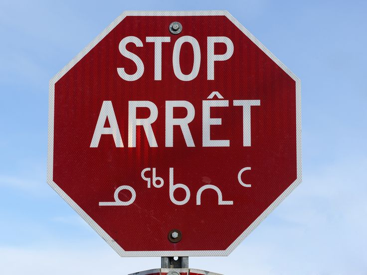 Stop sign in downtown Iqaluit, in 3 languages (English, French & Inuktitut).