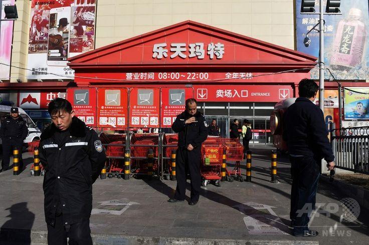 米軍による最新鋭迎撃システム「高高度防衛ミサイル(THAAD)」が韓国に配備されたことを受け、中国政府による韓国製品のボイコットなどの影響で閉鎖した北京 Beijing 베이징 のロッテマート  ( 乐天玛特 Lotte Mart 樂天瑪特 롯데마트 ) で警備する警官(2017年3月9日撮影)。(c)AFP/Greg Baker