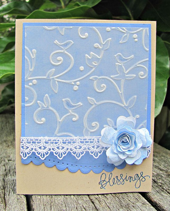 """By Dawn Turley. Dry emboss vellum in Cuttlebug """"Birds and Swirls"""" folder. Punch or die cut border of blue piece. Layer vellum piece over blue piece. Add lace. Attach to card base. Add flower and sentiment."""