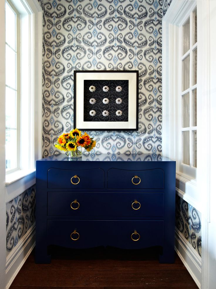 Immediately upon entering, on the right is a Jacqui four-drawer dresser in indigo. The dresser is framed by blue, navy, and white wallpaper. The pulls of the dresser are in gold.