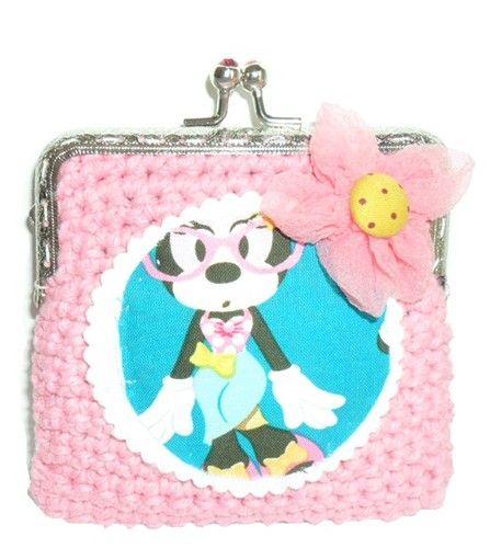 Carteira feita em linha barbante na cor rosa claro. Fecha com fecho metálico e a decorar tem uma aplicação em feltro da Minnie. Tem ainda a decorar, uma flor rosa em organza. Tamanho aproximado: 10,5cm x 11cm Preço: 5€