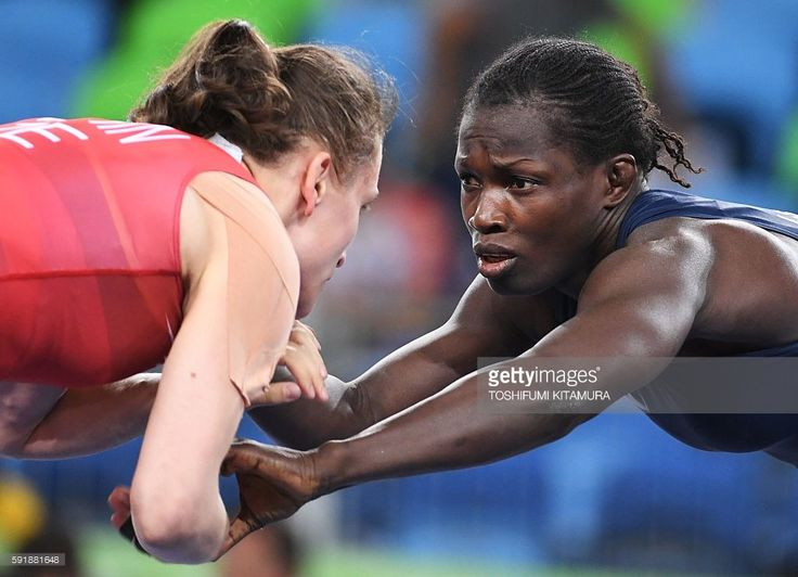 Azerbaijan's Natalya Sinishin (red) wrestles with Senegal's Isabelle Sambou in their women's 53kg freestyle repechage round 2 match on August 18, 2016, during the wrestling event of the Rio 2016 Olympic Games at the Carioca Arena 2 in Rio de Janeiro. / AFP / Toshifumi KITAMURA