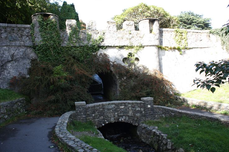 Antiga Ponte do Chifre no Parque Florestal Tollymore em Bryansford, Irlanda do Norte, Reino Unido.  A ponte cruza um pequeno córrego e  é atravessada por uma estrada de cascalho. O fluxo abaixo da ponte é coberto com um passeio de placa conectado a um caminho. Foi construída por volta de 1770 pelo 1º ou 2º conde de Clanbrassil.  Fotografia: Ardfern.