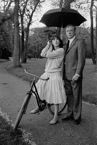 Isabelle Adjani rides a bike. Yves Montand holds an umbrella.
