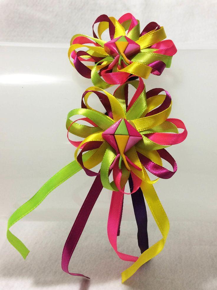 Em um modelo que foge dos tradicionais chapéus caipiras, essa linda tiara com 2 flores feitas em cetim com fios soltos na parte inferior e botões juninos é um charme para adultos e crianças.    Além das cores vivas e alegres que você pode escolher para o modelo, a tiara de 5mm em metal também é e...