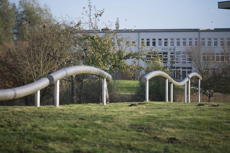#Flensburg Klangkünstler Ulrich Eller schuf für den Hochschulcampus in Flensburg eine permanente Klangskulptur aus sechs gebogenen Rohrsegmenten und integrierter Zuspieltechnik.