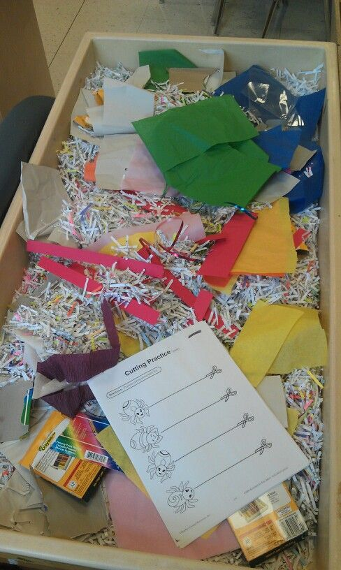 Cutting Table: Shredded paper, tissue paper, string, ribbon, cardboard, plastic and some cutting practice paper. Fine motor skills.