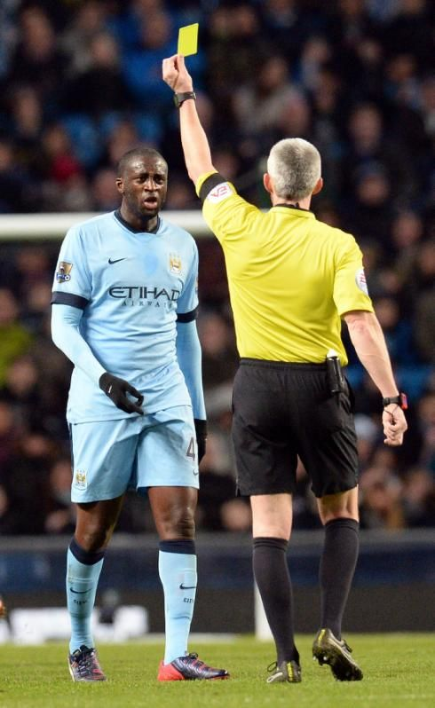 Manchester City's Yaya Toure (L) receives a yellow card during their English Premier League match against Newcastle United, at The Etihad Stadium in Manchester, on February 21, 2015