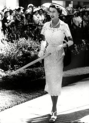 Queen Elizabeth almost always wore full-skirts, but this is a rare photo of her wearing a lovely knee-length lace dress with a face-revealing hat, and elbow-length white gloves.  queen-elizabeth-1950s-lace-dress