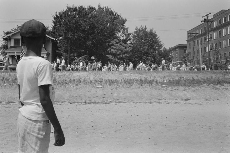 """A young boy watching a group of people, some carrying American flags, march past to protest the admission of the """"Little Rock Nine"""" to Central High School in Little Rock, Arkansas, August 20, 1959. (Photo by Reuters/Library of Congress)"""
