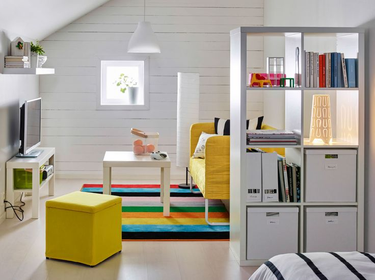 a white shelving unit used as a room divider combined with a sofa and footstool with yellow covers.