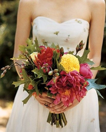 In keeping with the wedding's mountain locale, the bridal bouquet of roses, cactus dahlias, and pom-pom dahlias is accented with oak leaves and acorns.