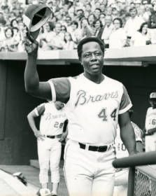 """Atlanta Braves baseball player Hank Aaron tips his hat after hitting his 700th homerun, Atlanta, Georgia, July 21, 1973. """"The biggest story in local sports thus far in 1982 is Hank Aaron's induction into baseball's Hall of Fame a couple of weeks ago. Hammerin' Hank was in his glory days after hitting homerun number 700 above."""" AJCP553-024a, Atlanta Journal Constitution Photographic Archives. Special Collections and Archives, Georgia State University Library."""