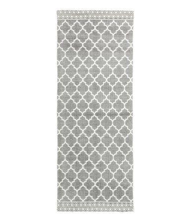 Grå. En avlång matta i vävd bomullskvalitet med tryckt mönster på ovansidan.