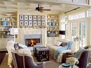 Sea and Sky Room: Inspired by the locale, this living room incorporates shades of blue, cream, and gray throughout. Buttery-colored paint highlights the architectural details, from the coffered ceiling to the redded mantel. Patterned wallpaper that's been carefully applied to the backs of two built-in bookcases adds custom style.
