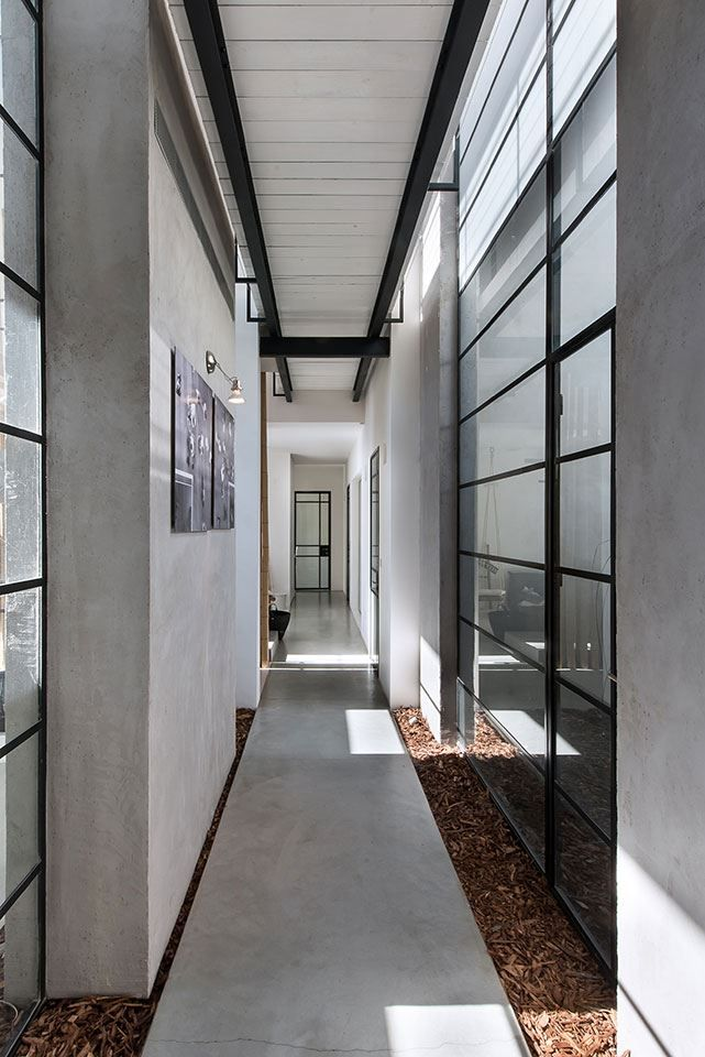 This house designed by Neuman Hayner Architects is composed of two cubes separated by a passage and combining into an L-shaped house. The interiors features several hanged items, like lightings, chairs and beds #corridor
