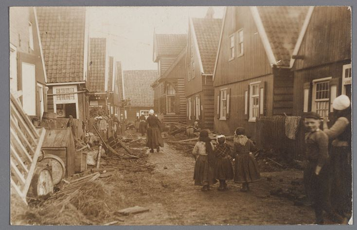 Chaos in de Kerkbuurt na de watersnoodramp. Vrouwen en kinderen in klederdracht. De Straat in de Kerkbuurt. De jongen rechts is K. Schipper (Ka Nies) Watersnood 1916 #NoordHolland #Marken
