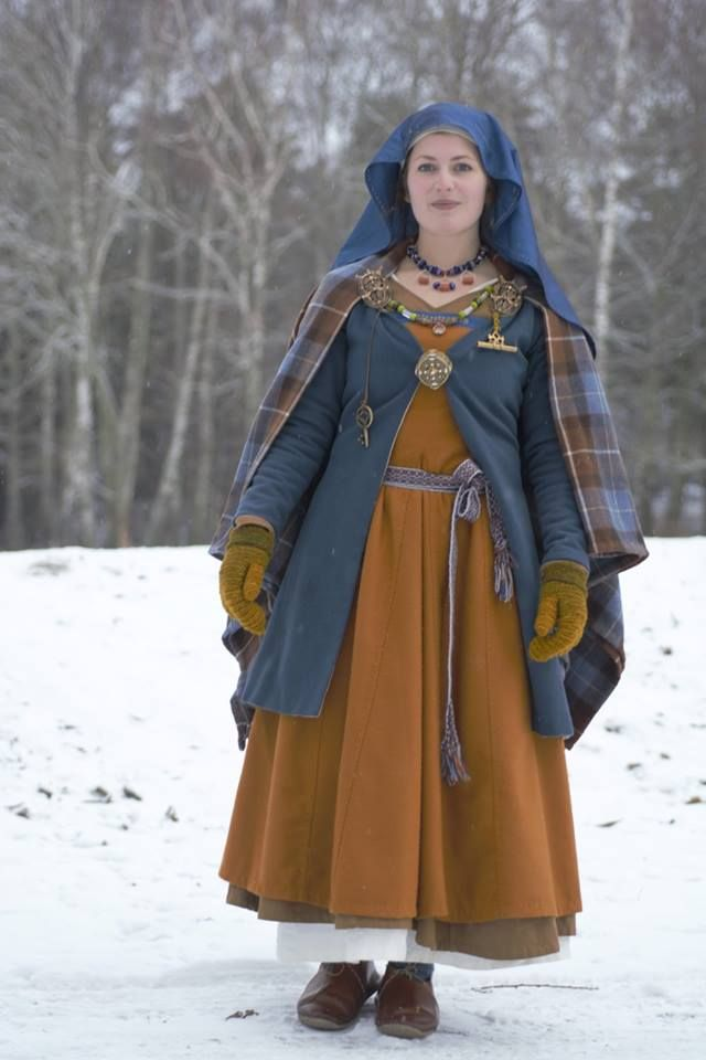Viking reenactment: a linen undergarment, a brown woolen dress with long sleeves, and an apron dress with silk decorations and metal posaments. Also a blue coat, a checkered shawl and a pair of needle bound mittens (dyed with yellow leek). On my head I'm wearing a silk veil, fastened to a linen cap with two needles. Everything is hand sewn with waxed linen thread. The jewelry is mainly Birka (as the rest of the outfit), but the large box brooch in front is based on a find from Gotland.