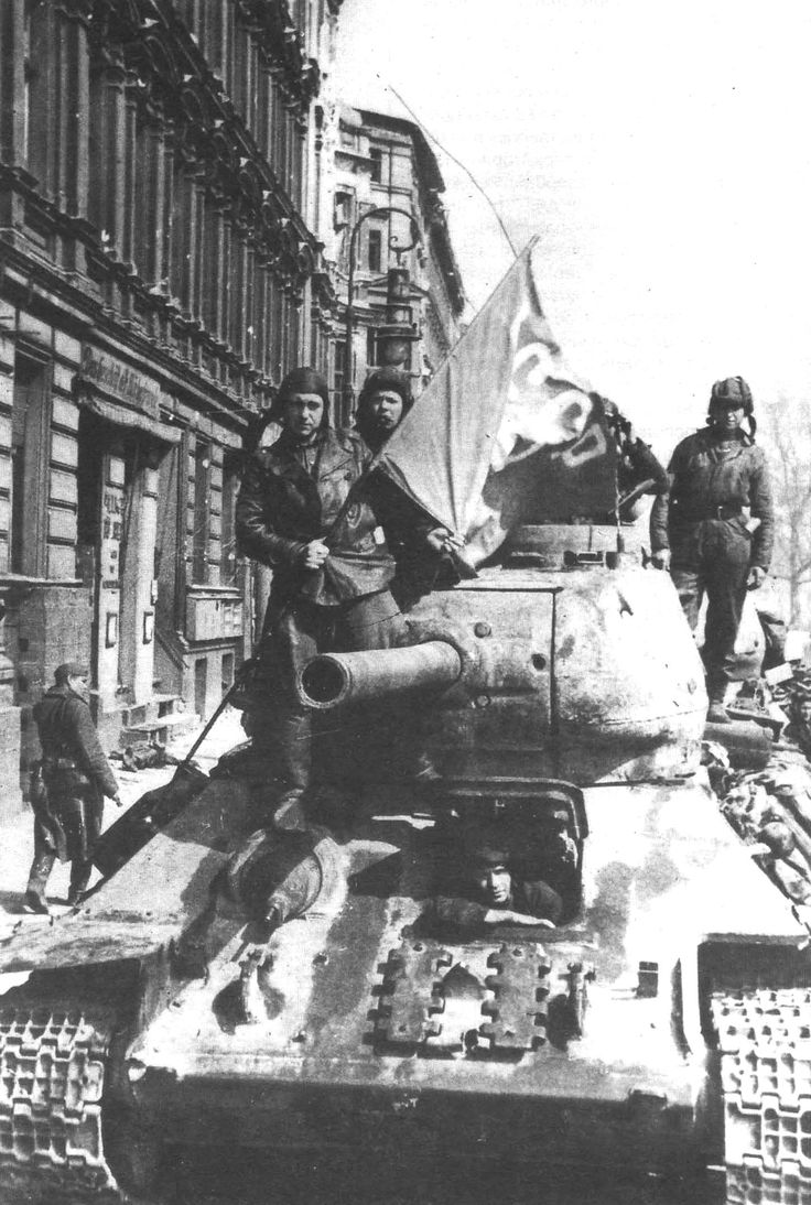 Soviet T-34 tank in the streets of Berlin after the end of the battle. Note the spare caterpillar links attached in front of the driver's hatch.