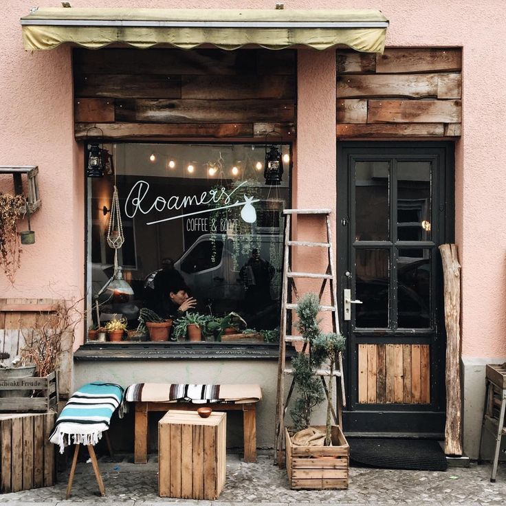 Love all of this. Handwritten font on window, fairy lights slung low, plants on the window sill, wooden boards above the door frame.