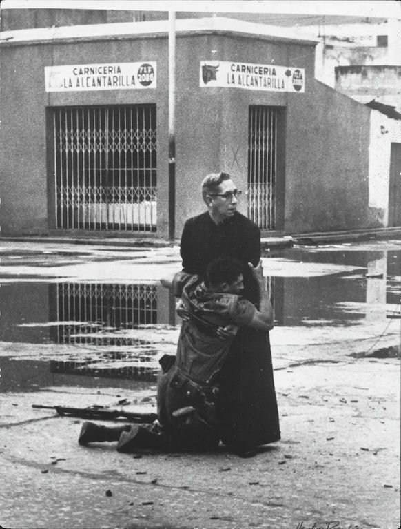 1962 - Priest Luis Padillo offers last rites to a loyalist soldier who is mortally wounded by a sniper during military rebellion against President Bétancourt at Puerto Cabello naval base in Venezuela. (Héctor Rondón Lovera)