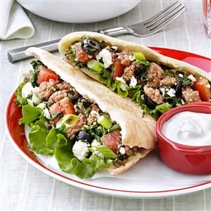 Beef & Spinach Gyros Recipe -A gyro typically is made of meat, often lamb, roasted on a spit and served sandwich style in folded pita bread. It's topped with tomato, onion and a Greek-style yogurt. Tradition takes a slight twist with the use of ground beef, spinach and ripe olives. Opa! —Mary Johnson, Coloma, Wisconsin