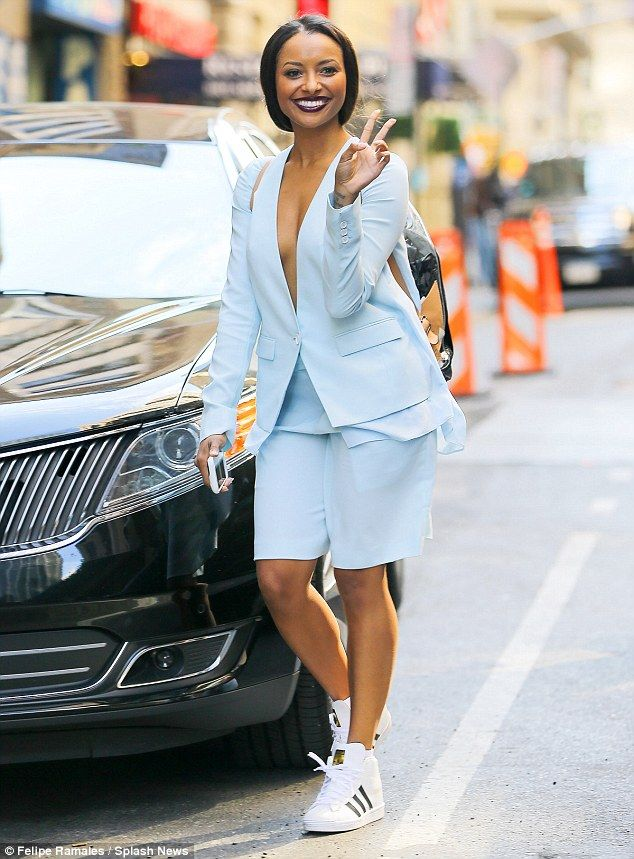 Love and peace out: A smiling Kat Graham wore a pale blue jacket that very clearly revealed she had left her bra back in her hotel as she strolled in New York on Friday