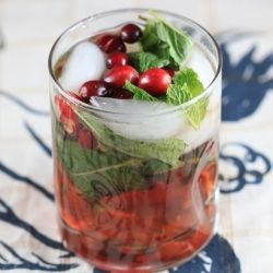 A winter mojito with dark rum, cranberry and mint